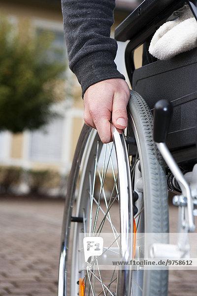 Hand des jungen Mannes auf Speiche des Rollstuhls