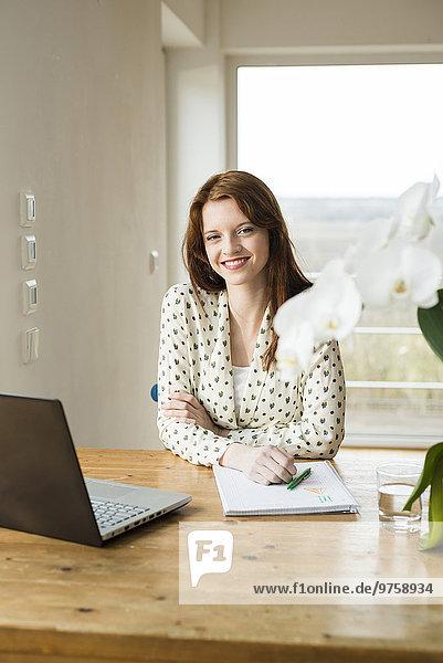 Lächelnde junge Frau mit Laptop am Holztisch