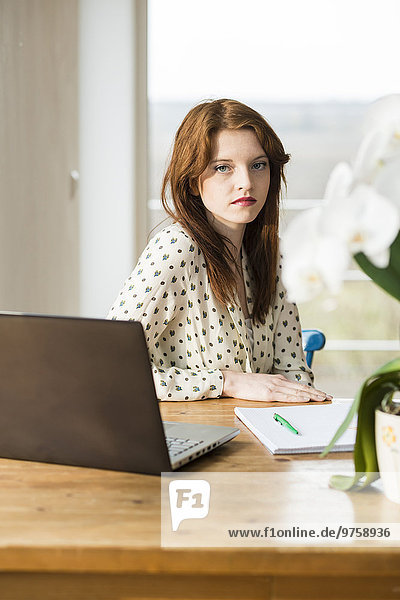 Junge Frau mit Laptop am Holztisch