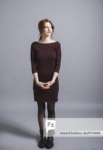 Lächelnde junge Frau im Kleid schaut nach oben