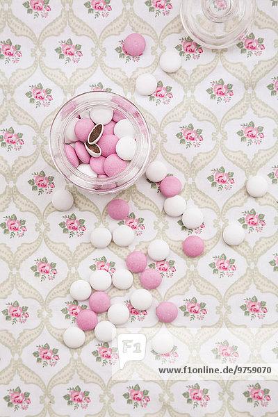 Glas mit rosa und weißen Schokoladenknöpfen auf floral gemustertem Stoff