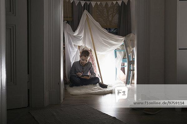 Junge sitzt abends im selbstgebauten Zelt zu Hause und benutzt ein digitales Tablett.