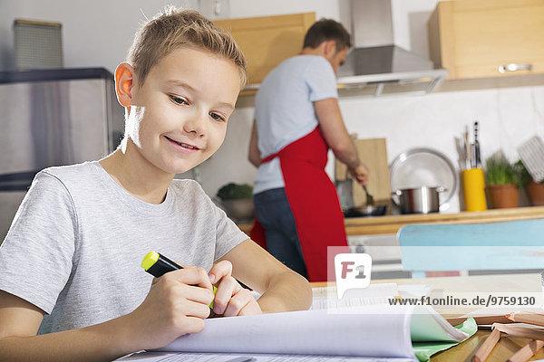 Lächelnder Junge sitzt am Küchentisch und macht seine Hausaufgaben.