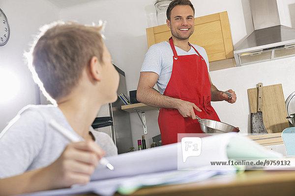 Vater bereitet das Essen zu  während sein Sohn seine Hausaufgaben macht.