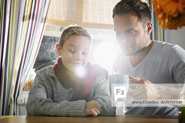 Junge  der mit seinem Vater in der Küche sitzt.