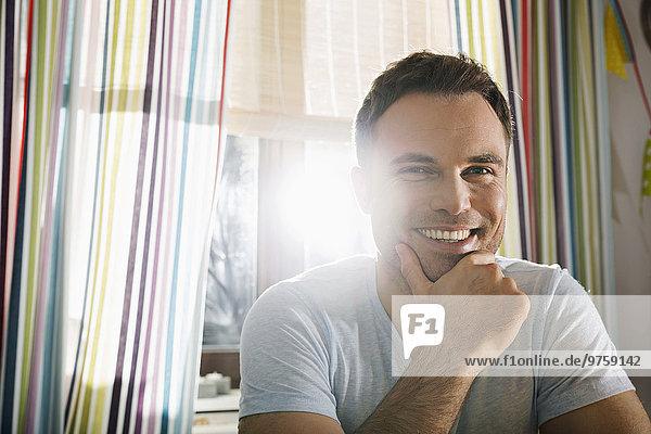 Porträt eines lächelnden Mannes in der Küche