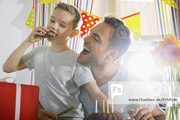 Vater und Sohn essen Geburtstagstorte