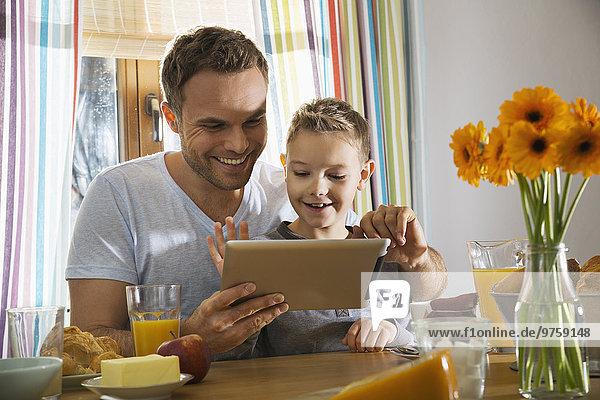 Vater und Sohn sitzen am Frühstückstisch mit Hilfe eines digitalen Tabletts.