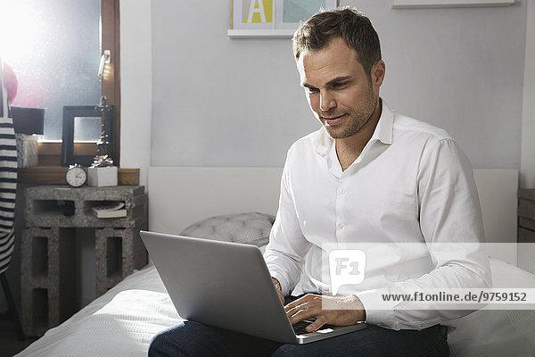 Mann sitzt auf dem Bett zu Hause mit Laptop