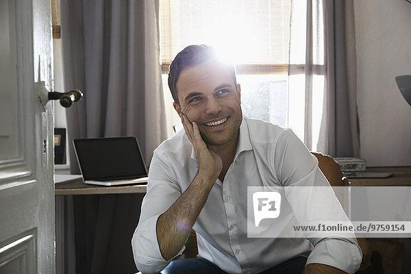 Porträt eines lächelnden Mannes in seinem Home Office
