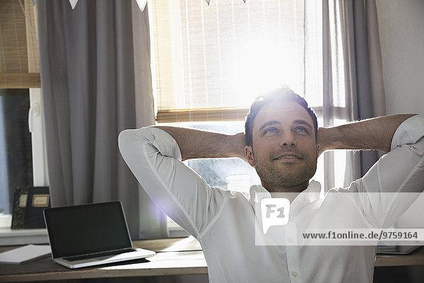 Porträt eines glücklichen Mannes mit den Händen hinter dem Kopf in seinem Home-Office