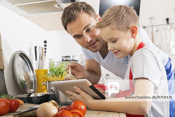 Vater und Sohn kochen gemeinsam mit dem digitalen Tablett