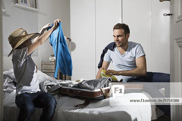 Vater und Sohn sitzen auf dem Bett und packen den Koffer.