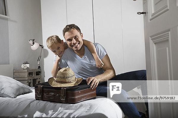 Vater und Sohn auf dem Bett sitzend mit Koffer und Strohhut