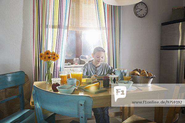 Junge sitzt am Frühstückstisch mit dem Smartphone