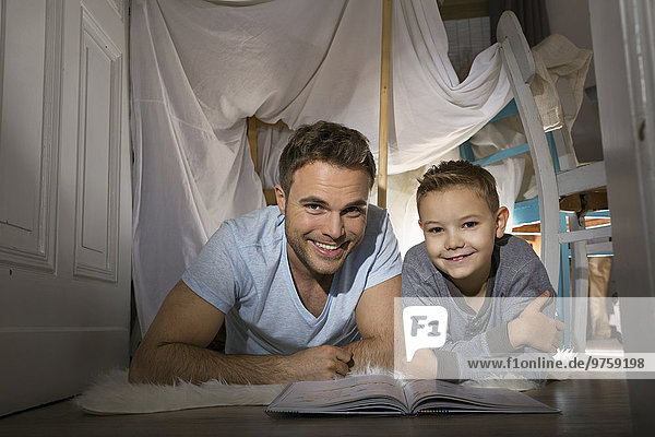 Vater und Sohn mit Buch auf dem Boden liegend im selbstgebauten Zelt zu Hause