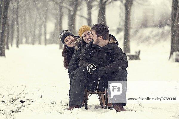 Drei Freunde sitzen im Winter auf dem Schlitten
