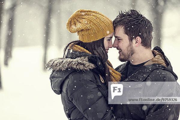 Glückliches junges Paar Kopf an Kopf im Winter