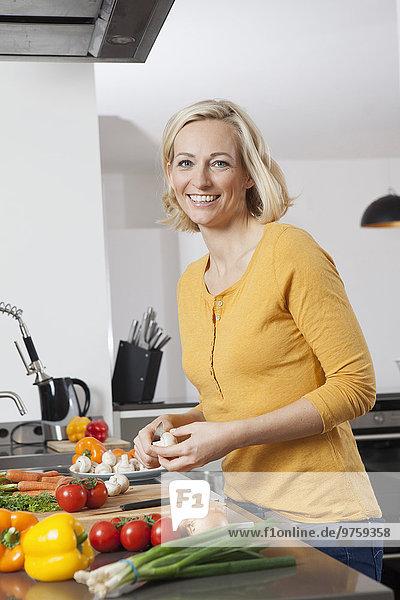 Lächelnde Frau beim Kochen in der Küche