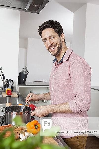 Lächelnder Mann beim Kochen in der Küche