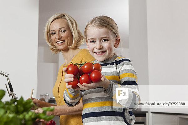 Mutter mit Tochter mit Tomaten in der Küche
