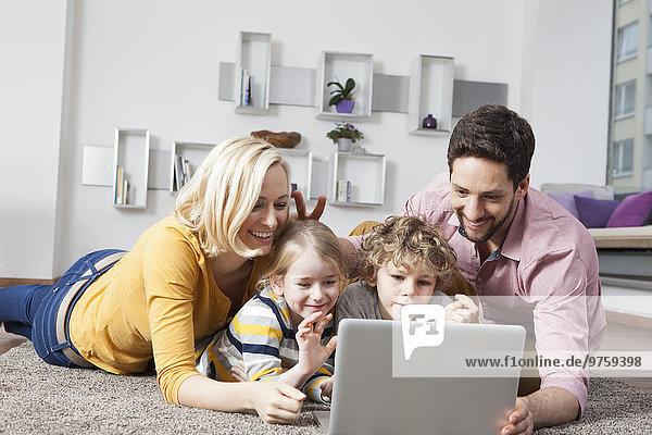 Glückliche Familie mit Laptop zu Hause