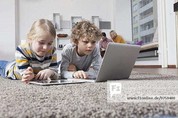 Geschwister auf dem Boden liegend mit Laptop und digitalem Tablett