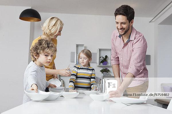 Familie deckt den Tisch
