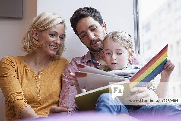 Vater und Mutter lesen Bilderbuch für Tochter