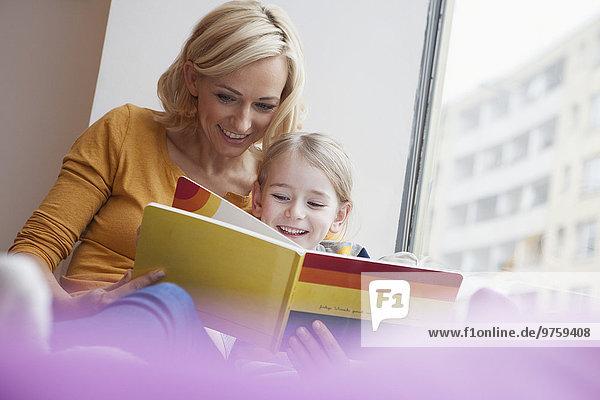 Mutter liest Bilderbuch für Tochter
