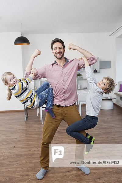 Vater trägt Sohn und Tochter auf den Armen