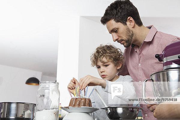 Vater und Sohn bereiten Geburtstagskuchen in der Küche vor