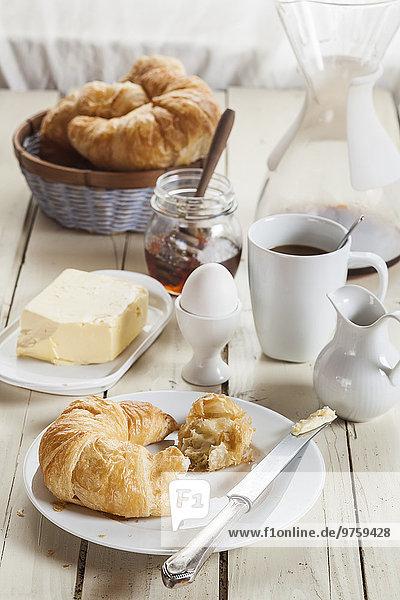 Frühstück mit Croissant  Ei  Kaffee  Honig und Butter Frühstück mit Croissant, Ei, Kaffee, Honig und Butter
