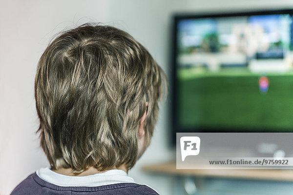 Junge schaut am Monitor und spielt Computerspiel