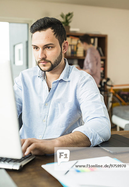 Young man working at computer at home