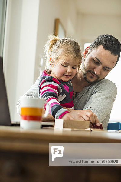 Vater und Tochter spielen ein Spiel am Holztisch