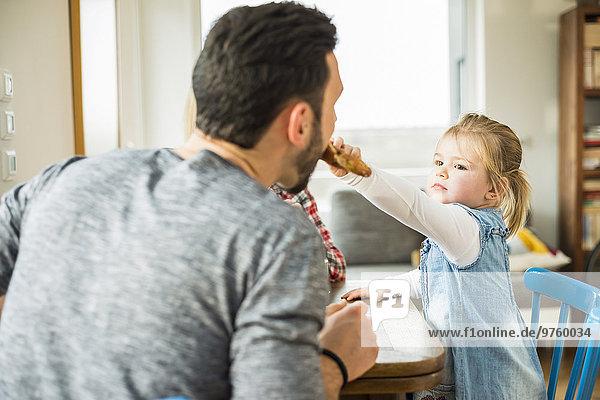 Tochter füttert Vater am Esstisch
