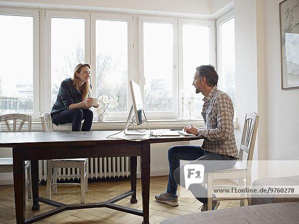 Deutschland  Köln  reifer Mann und erwachsene Tochter zu Hause  Arbeit am Computer