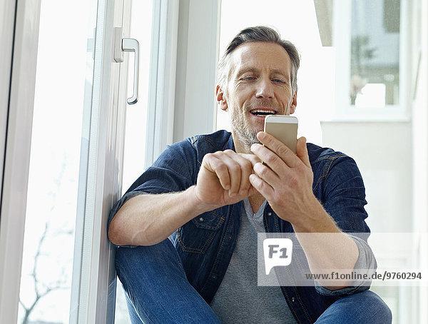 Deutschland  Köln  Erwachsener Mann am Fenster sitzend mit Smartphone Deutschland, Köln, Erwachsener Mann am Fenster sitzend mit Smartphone