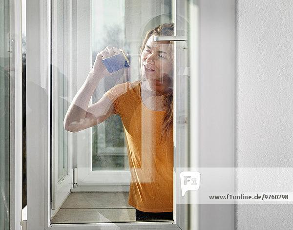 Deutschland  Köln  Junge Frau schaut aus dem Fenster Deutschland, Köln, Junge Frau schaut aus dem Fenster