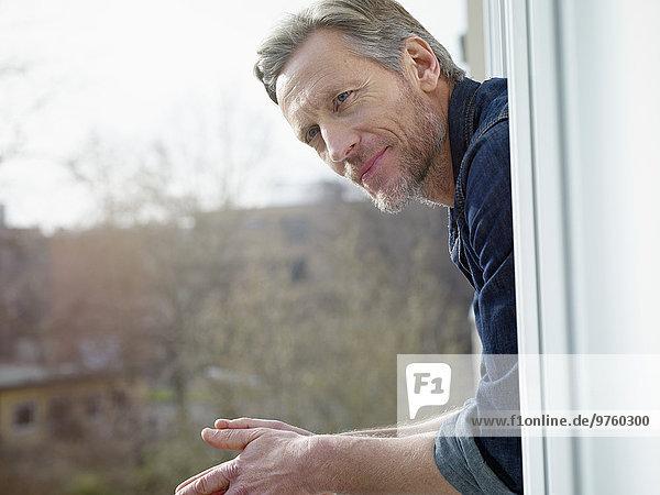 Deutschland  Köln  reifer Mann aus dem Fenster schauend Deutschland, Köln, reifer Mann aus dem Fenster schauend