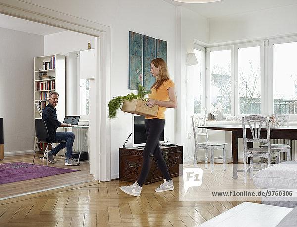 Erwachsener Mann  der von zu Hause aus arbeitet  erwachsene Tochter  die eine Kiste mit Gemüse trägt. Erwachsener Mann, der von zu Hause aus arbeitet, erwachsene Tochter, die eine Kiste mit Gemüse trägt.
