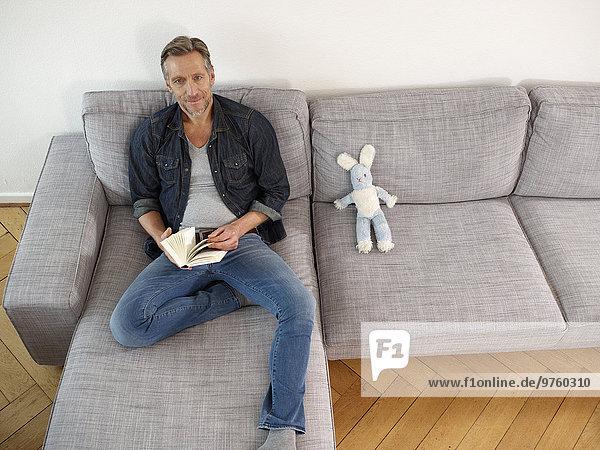 Erwachsener Mann auf Sofa sitzend  Buch haltend Erwachsener Mann auf Sofa sitzend, Buch haltend