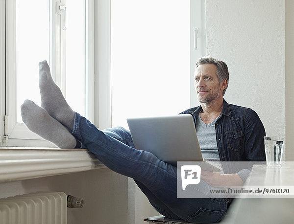 Deutschland  Köln  reifer Mann am Fenster sitzend mit Laptop  Füße oben