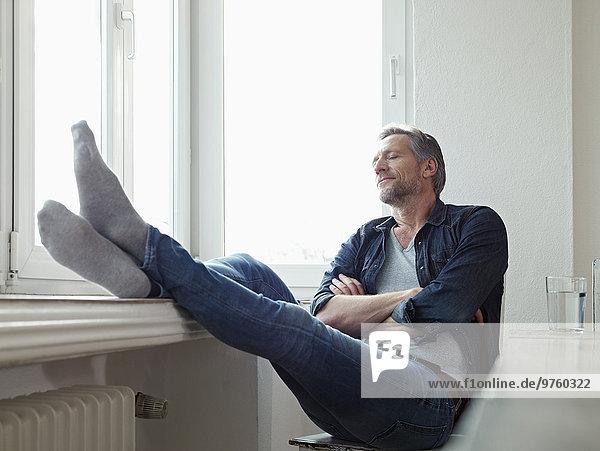Deutschland  Köln  reifer Mann am Fenster sitzend  Augen geschlossen Deutschland, Köln, reifer Mann am Fenster sitzend, Augen geschlossen