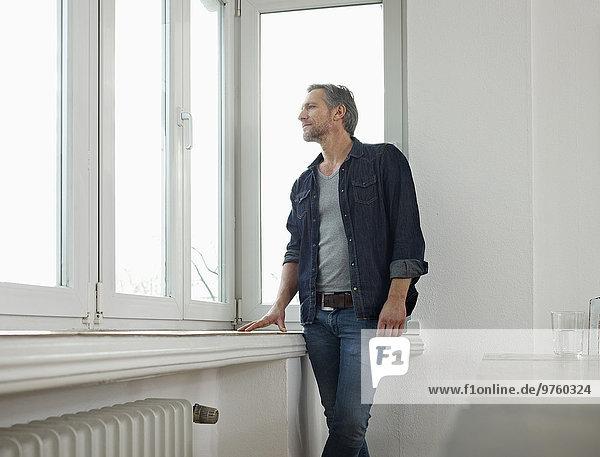 Deutschland  Köln  Erwachsener Mann am Fenster stehend  aus dem Fenster schauend Deutschland, Köln, Erwachsener Mann am Fenster stehend, aus dem Fenster schauend