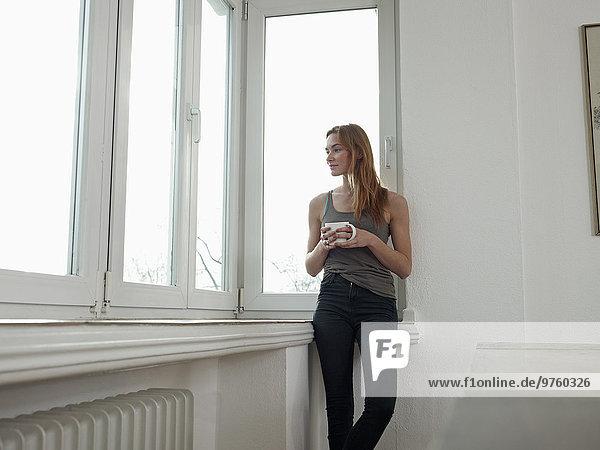 Deutschland  Köln  Junge Frau steht am Fenster  schaut hinaus