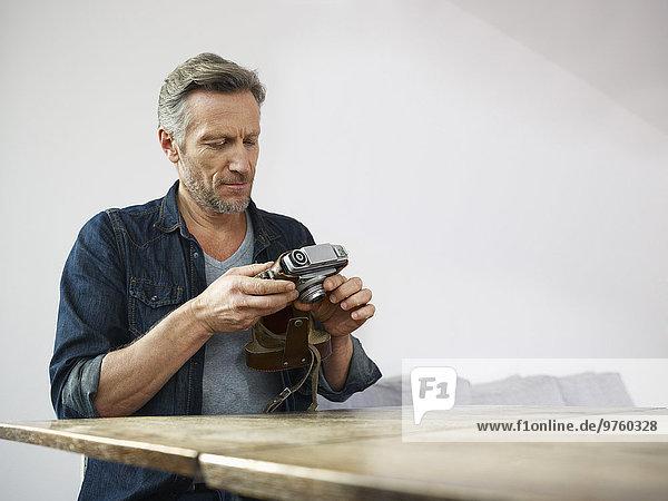 Erwachsener Mann am Tisch sitzend mit alter Kamera Erwachsener Mann am Tisch sitzend mit alter Kamera