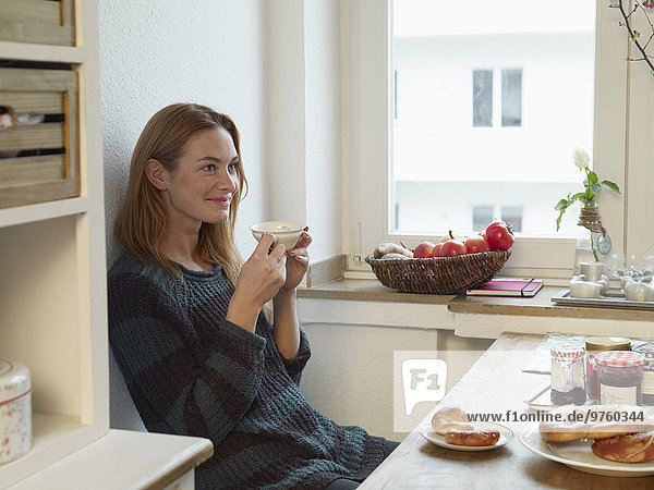 Young woman sitting in kitchen  having breakfast