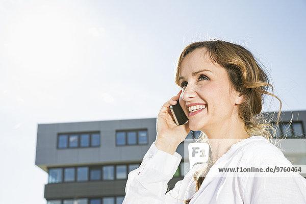 Lächelnde Geschäftsfrau telefoniert mit ihrem Smartphone